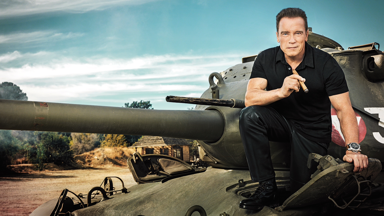 Arnold Schwarzenegger, ever-present cigar in hand, climbing into his own personal tank in Santa Clarita, California.