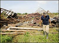 A farmer walks next to a tobacco warehouse demolished by Hurricane Wilma in the town of San Luis, southern Cuba.