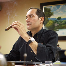 Guillermo Len in his office, puffing on a cigar. Len is the third-generation owner and president of La Aurora S.A.