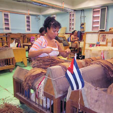The center vein in the tobacco leaf is stripped away, left, and the women doing the job make another.