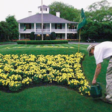A groundskeeper, right, waters the flowers at the end of Magnolia Drive in front of the main clubhouse.