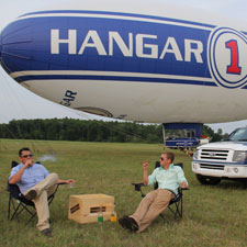 Diego Certuchi and Billy Gallaher relax with cigars between flights on the Hangar One blimp.