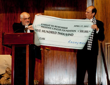 Shanken and Milken display a check for $500,000 to fight prostate cancer.